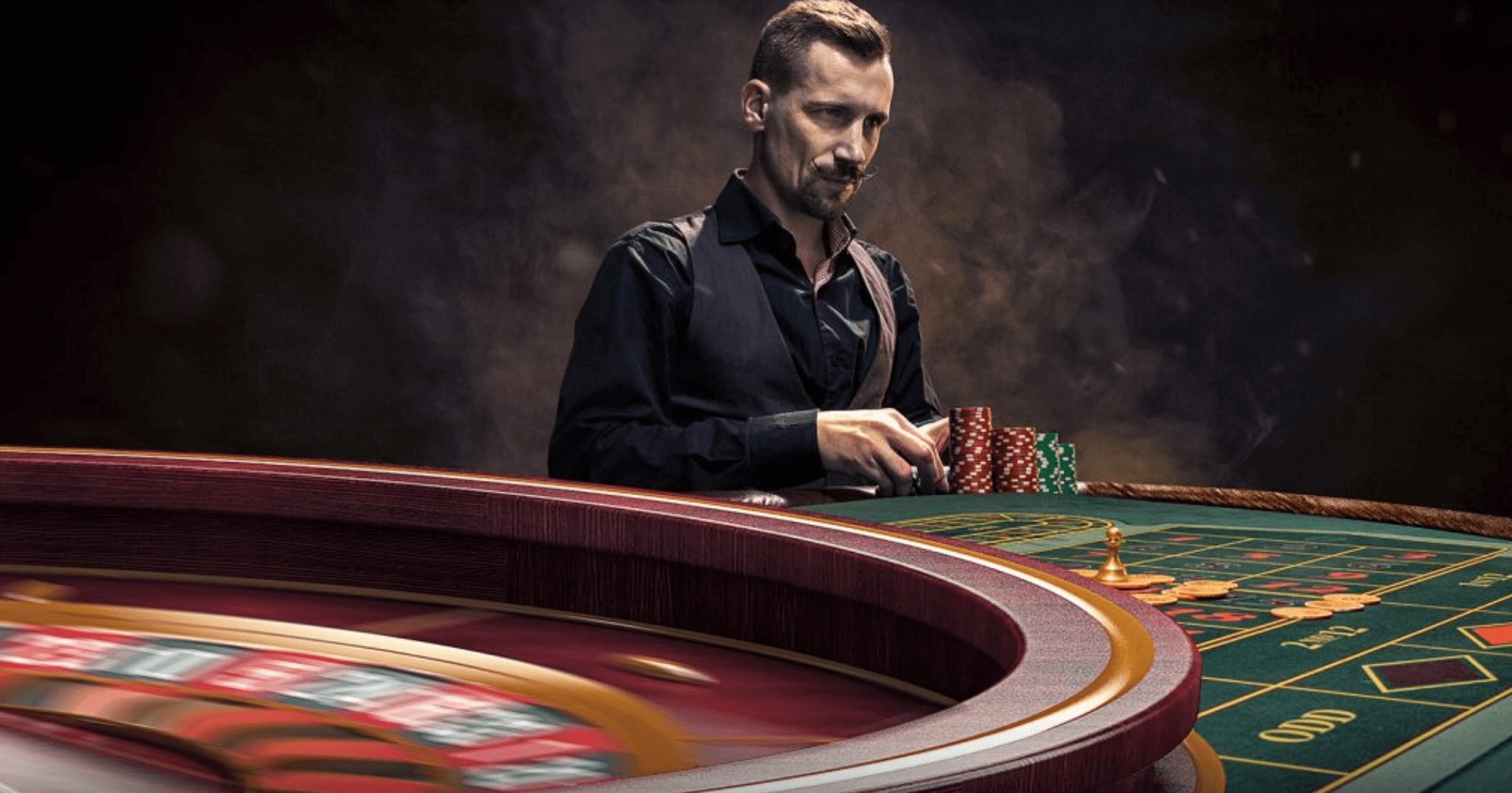 man at a roulette table placing bets