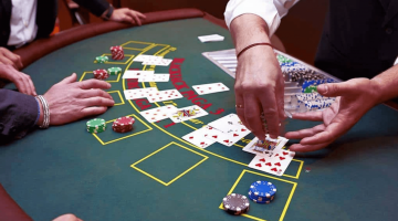 photo of a blackjack table with cards and chips