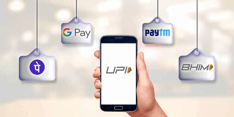 phone showing UPI and banner showing BHIM, Paytm, GPay and PhonePe