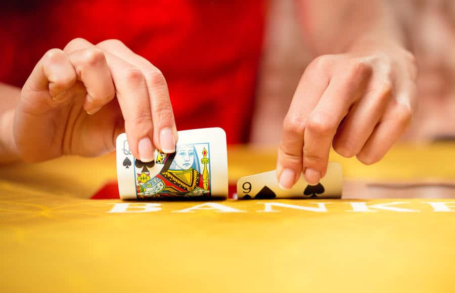 Baccarat dealer squeezing cards