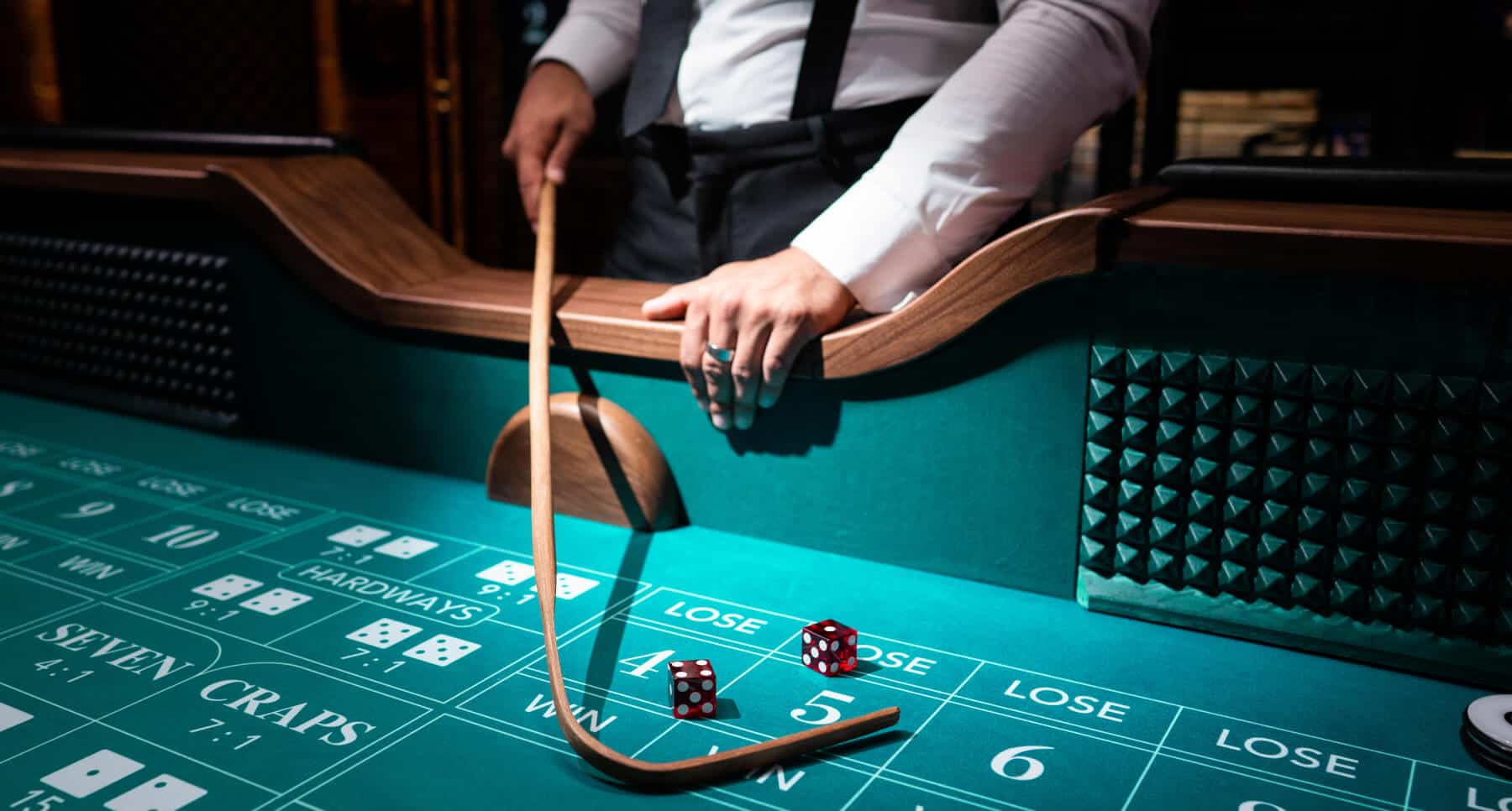 picture of a craps table, craps dealer, and two dice